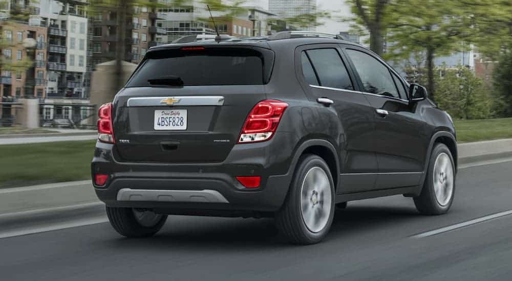 A dark grey 2020 Chevy Trax is driving down a city after winning the 2020 Chevy Trax vs 2020 Honda HR-V comparison.