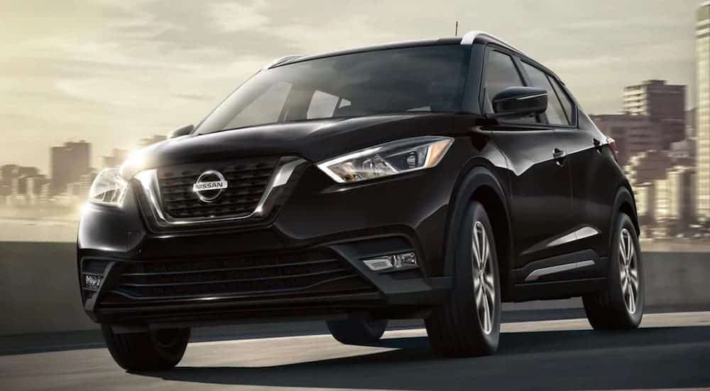 A black 2020 Nissan Kicks is driving away from a city skyline.