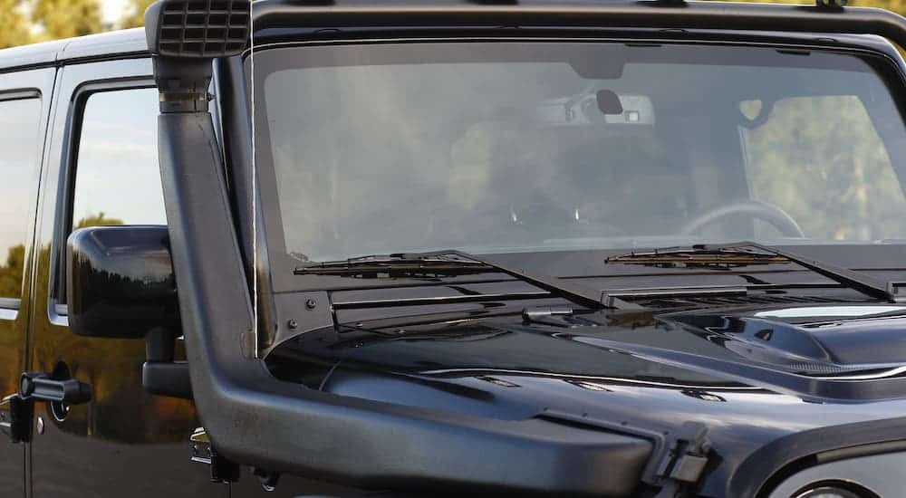 A snorkel air intake is attached to a black Jeep Wrangler Unlimited.