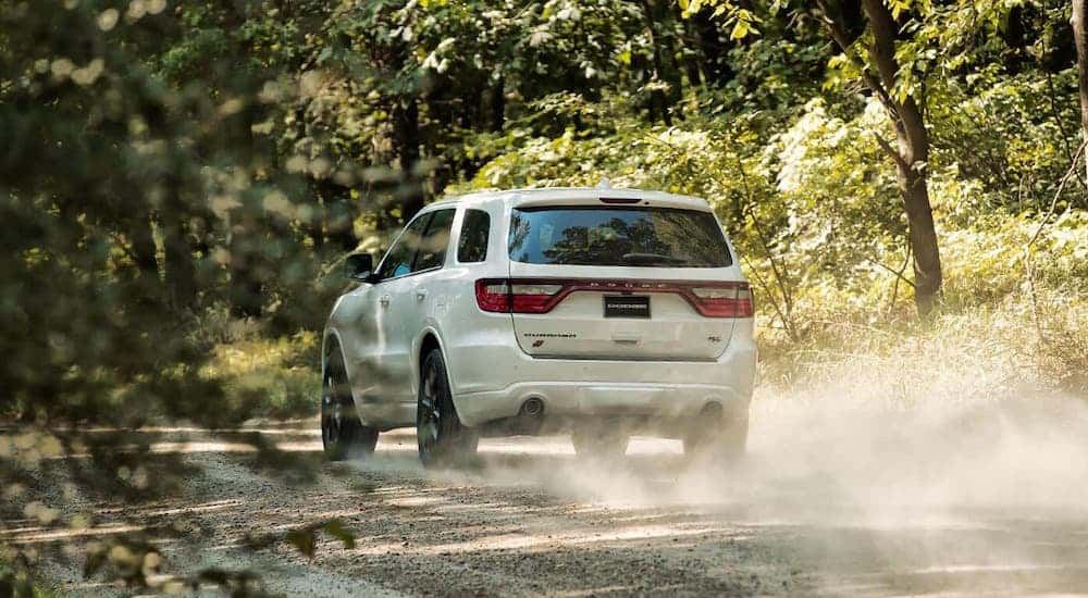 The rear is shown of a white 2020 Dodge Durango driving on a dirt road after losing the 2020 Ford Edge vs 2020 Dodge Durango comparison.