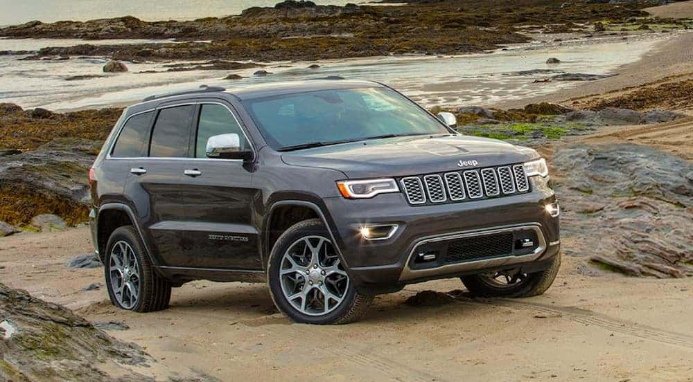 A grey 2020 Jeep Grand Cherokee is on the beach.