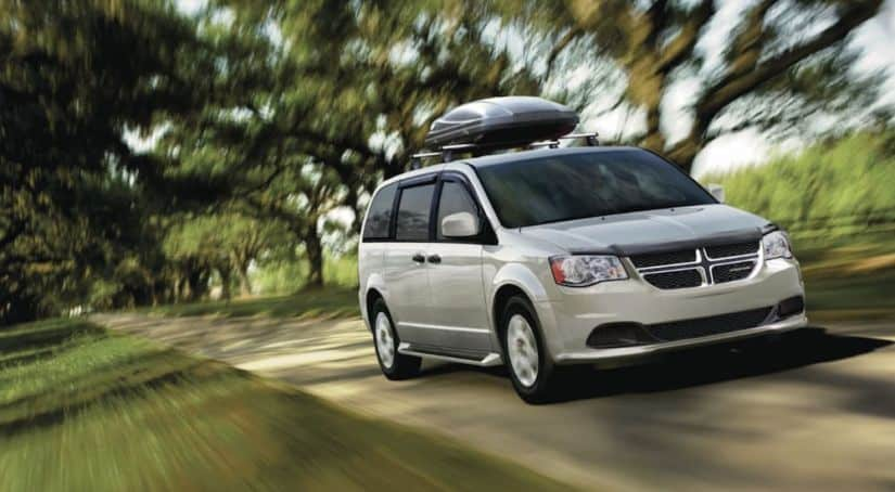 A silver 2020 Dodge Grand Caravan with a luggage compartment on top is driving on a tree-lined road.