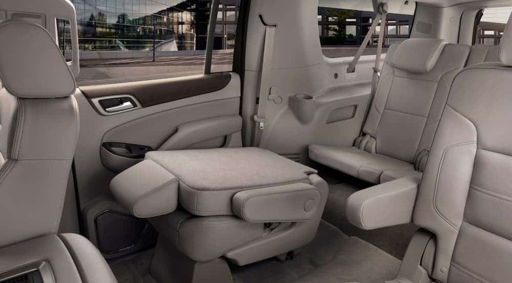 The middle row seat is folded down in the off-white interior of a 2020 GMC Yukon.