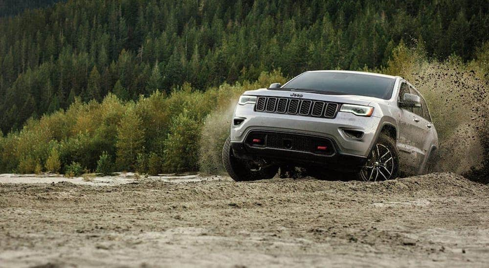 A silver 2020 Jeep Grand Cherokee Trailhawk is driving on a dirt trail in the woods after winning the 2020 Jeep Grand Cherokee vs 2020 Toyota 4Runner comparison.