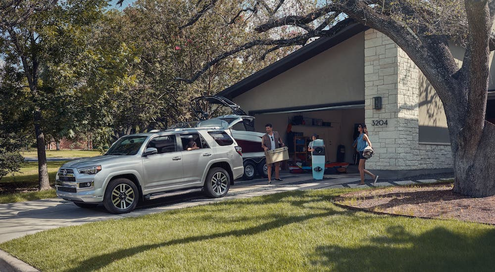 A family is loading gear into a silver 2020 Toyota 4Runner that is parked in a driveway.