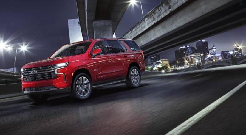 A red 2021 Chevy Tahoe RST is driving under a city bridge at night.