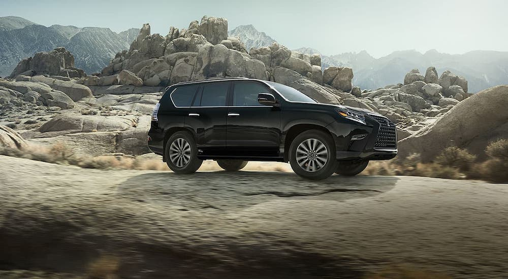 A black 2020 Lexus GX is driving over rocks in a desert.