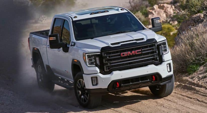 A popular truck for sale, a white 2020 GMC Sierra HD AT4, is shown from the front driving on a dirt road.