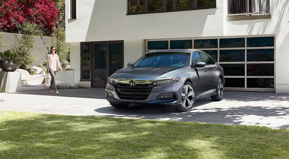 A woman is walking towards a gray 2020 Honda Accord Touring 2.0T that is parked in the driveway of a modern home.