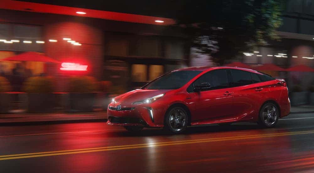 A red 2021 Toyota Prius is driving on a city street at night.