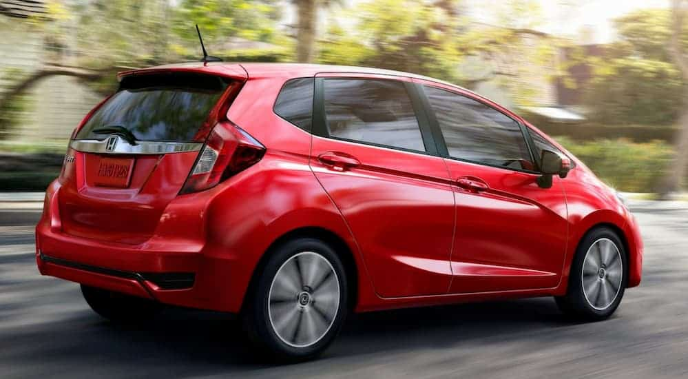 A red 2020 Honda Fit is driving through a neighborhood with trees.