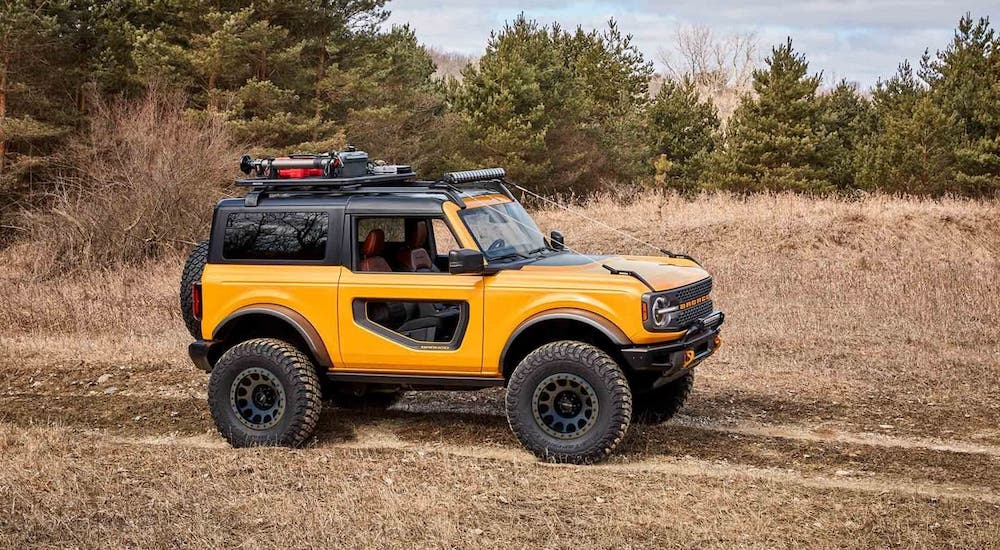 A yellow 2021 Ford Bronco 2-door is driving through a field.