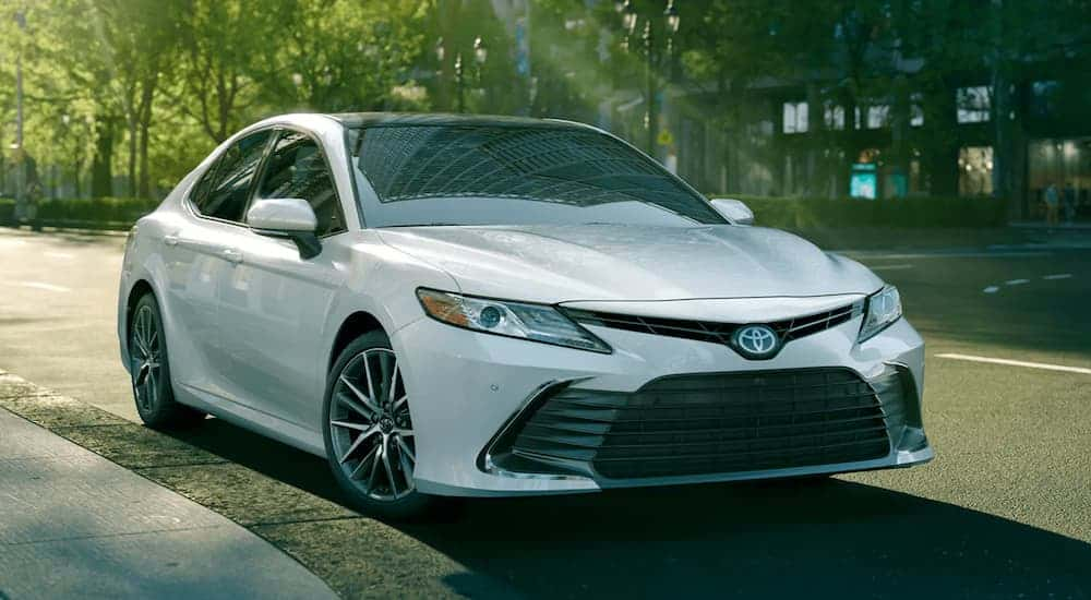 A white 2021 Toyota Camry is parked on a city street.