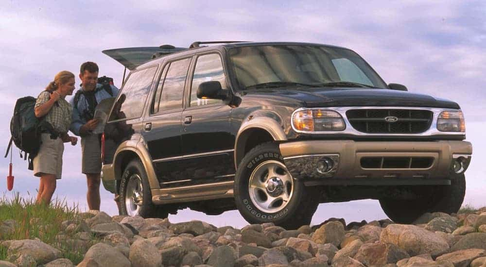 A couple is loading hiking gear into a black 2001 used Ford Explorer.