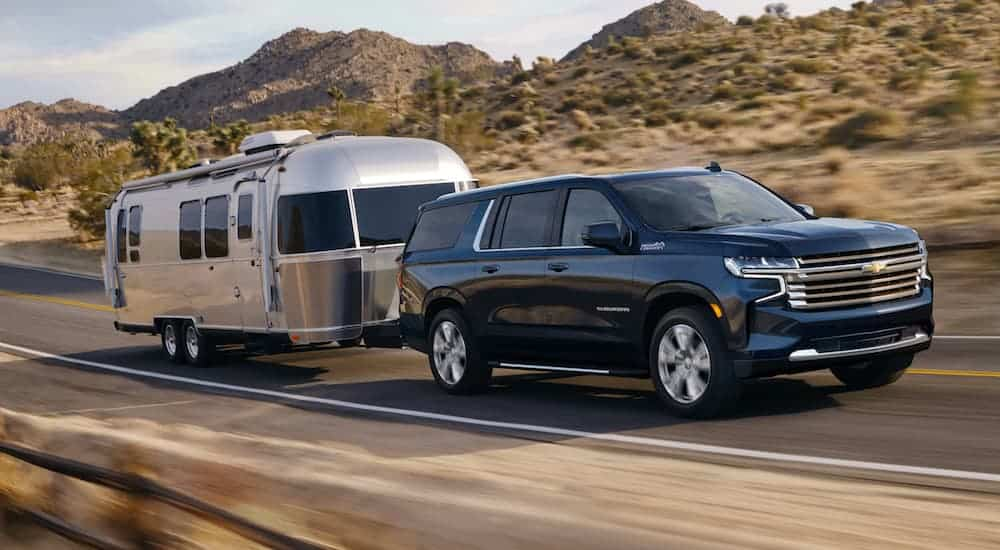 A blue 2021 Chevy Suburban is towing an Airstream past hills.