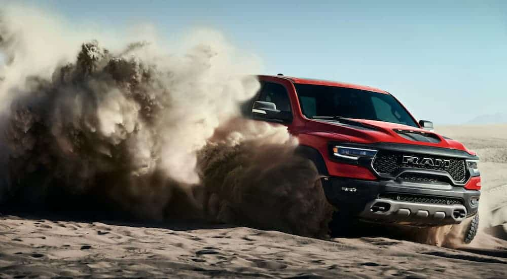 A red 2021 Ram 1500 TRX is kicking up sand while off-roading after winning the 2021 Ram TRX vs 2020 Ford Raptor comparison.