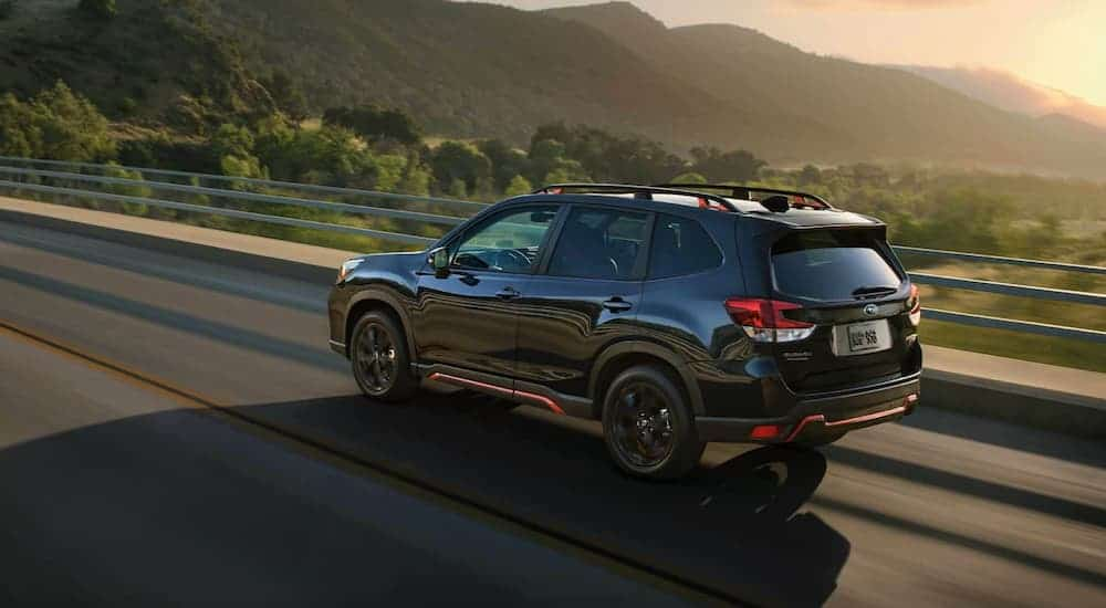 A black 2021 Subaru Forester is driving past mountains at sunset.