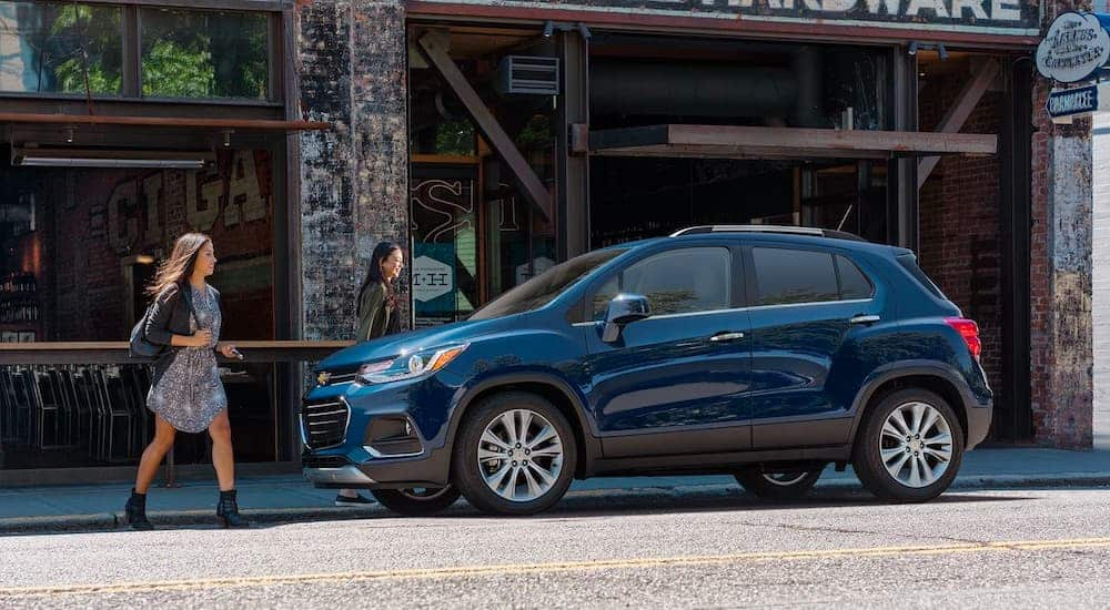 A blue 2021 Chevrolet Trax is parked in front of a store with two women approaching it.