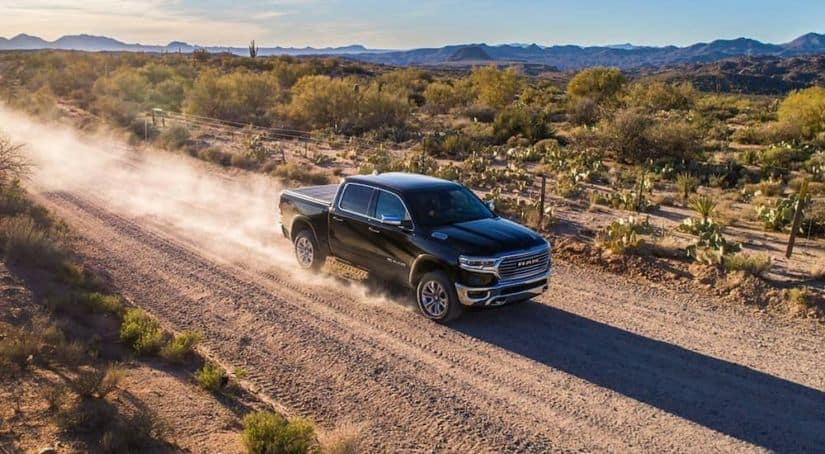 A black 2019 used Ram 1500 is driving down a dirt road kicking up some dust.