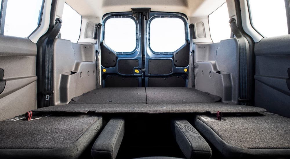 The seats are folded down in the back of a 2021 Ford Transit Connect and shown from the front of the vehicle.