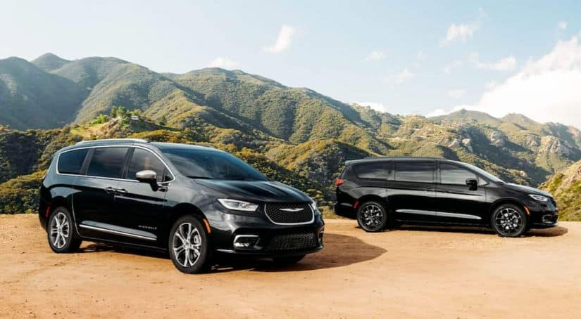 Two black 2021 Chrysler Pacificas are parked on dirt in front of tree-covered mountains.
