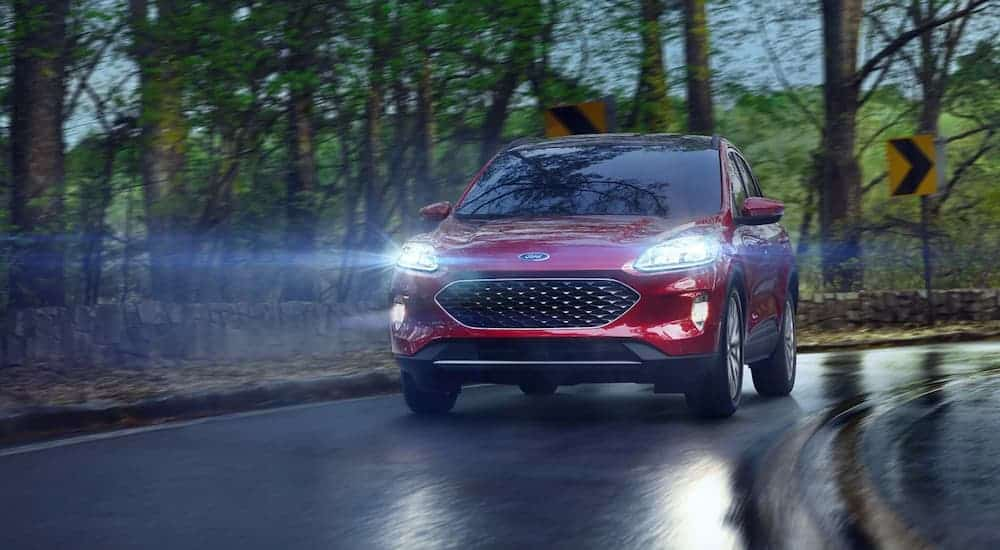A red 2021 Ford Escape is driving down a wet road with its headlights on.