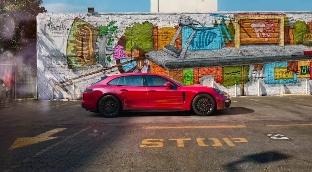 A red 2021 Porsche Panamera GTS is shown in profile with a mural in the background.