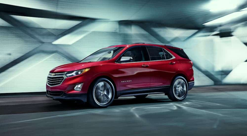 A red used 2018 used Chevy Equinox is shown in profile driving down a tunnel.