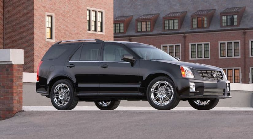 A black 2009 Cadillac SRX is parked in front of brick buildings after leaving the used luxury SUV dealer.