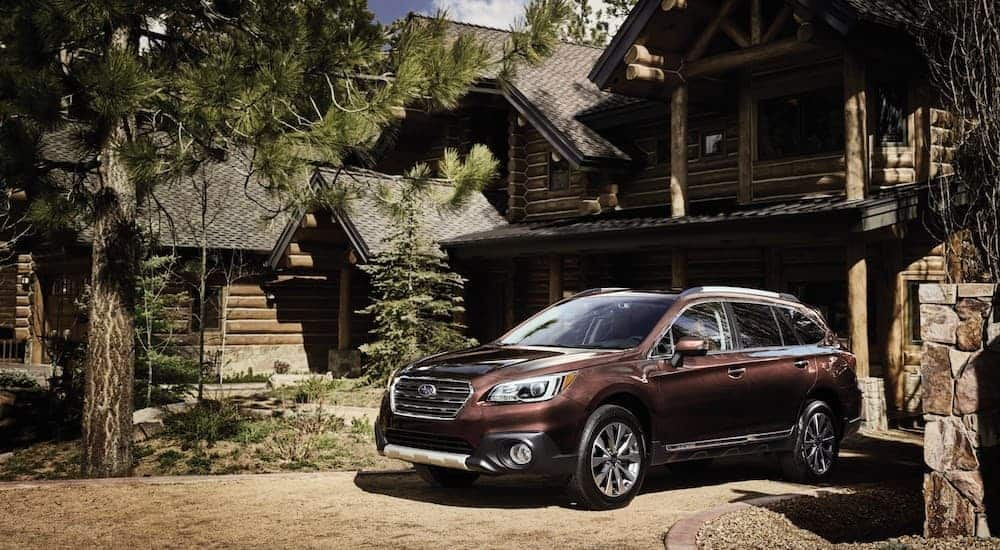 A brown 2016 Subaru Outback is parked in front of a log cabin.