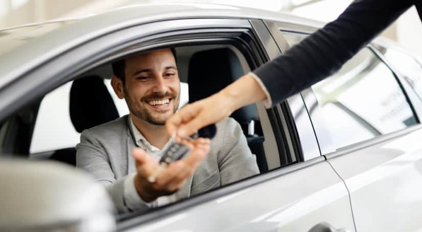 A salesperson is handing keys to a smiling man in a silver car.