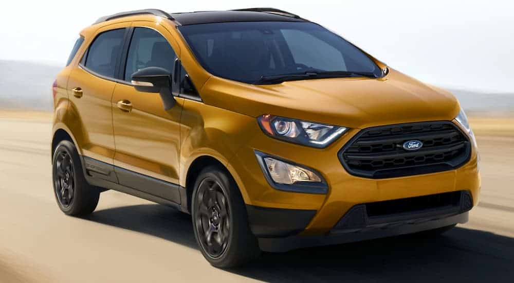 A gold 2021 Ford EcoSport is driving on a bright road with a blurred background.