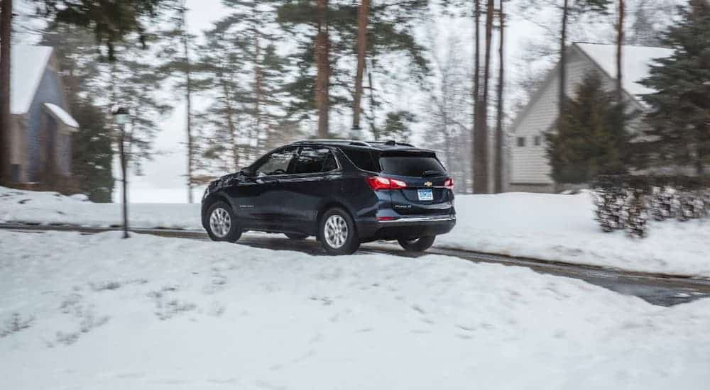 A blue 2021 Chevy Equinox is shown from a rear angle while driving on a snowy road.