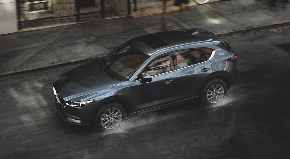 A black 2021 Mazda CX-5 is driving on a wet city street and shown from a high angle.