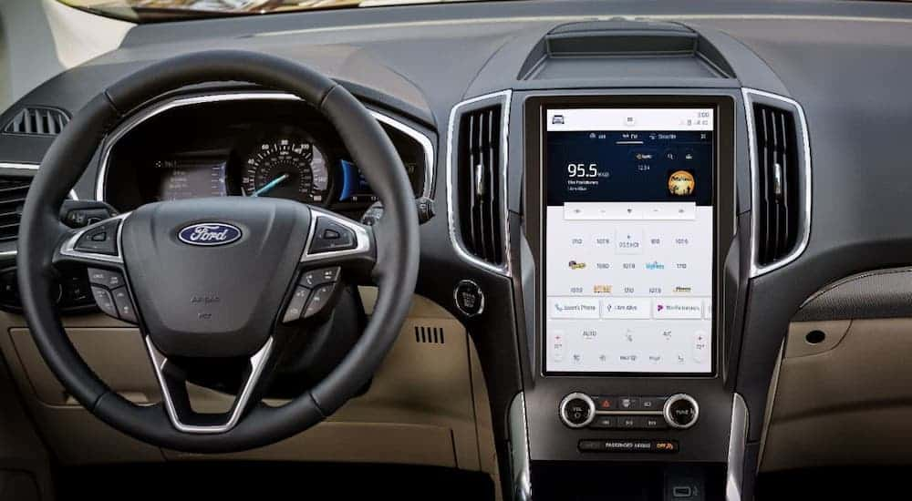 The steering wheel and large infotainment screen are shown in a 2021 Ford Edge at a Ford dealer.