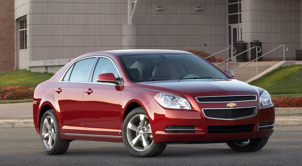 A red 2009 Chevy Malibu is shown angled right, parked in front of a concrete building.