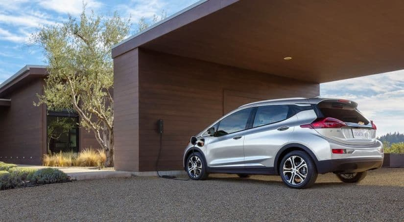A silver 2021 Chevy Bolt EV is shown from behind while charging at a modern house.