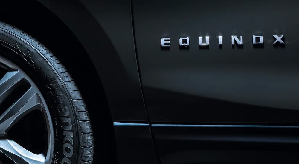 A close up shows the Equinox badge on a dark gray 2021 Chevy Equinox.