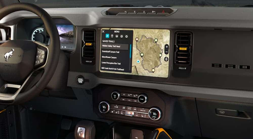 A close up shows the black interior and infotainment screen in a 2021 Ford Bronco Sport.