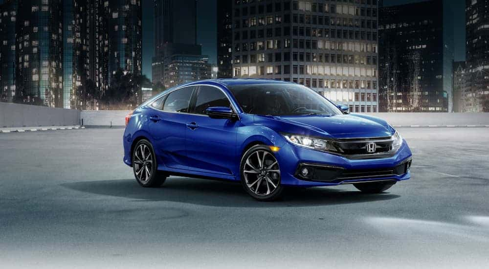 A blue 2021 Honda Civic is parked on a rooftop garage in a city at night.