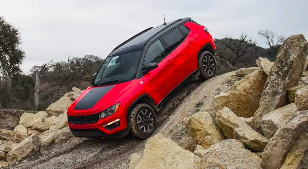 A red 2021 Jeep Compass Trailhawk is driving over rocks.