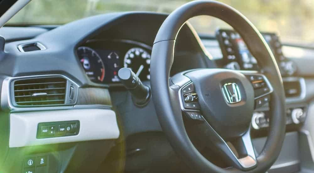A close up shows the steering wheel and black interior in a 2021 Honda Accord.