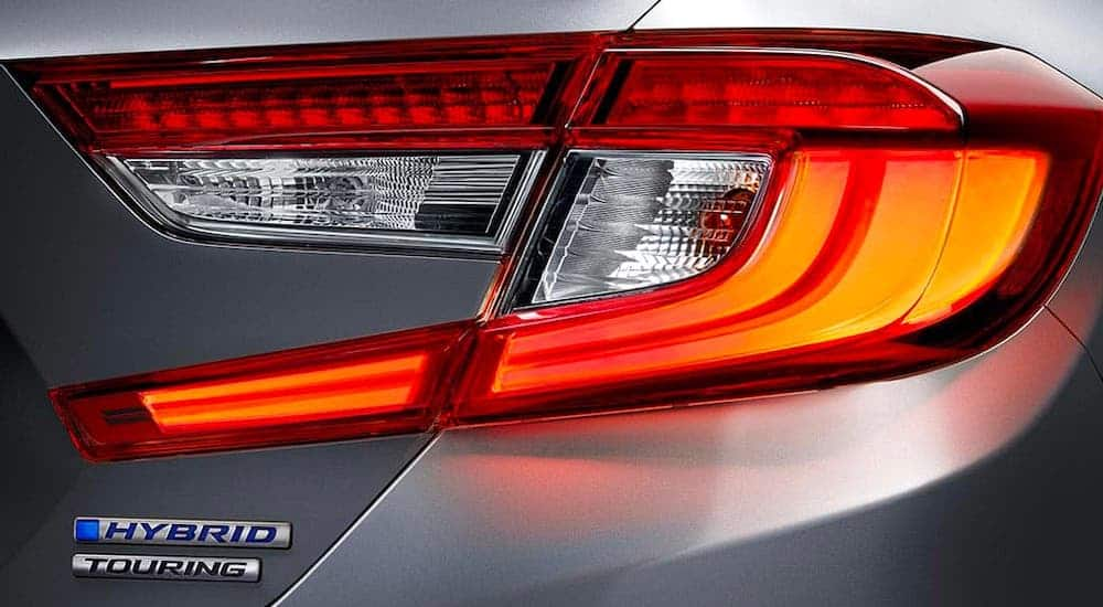 A closeup shows the taillight and Hybrid badging on a gray 2021 Honda Accord.