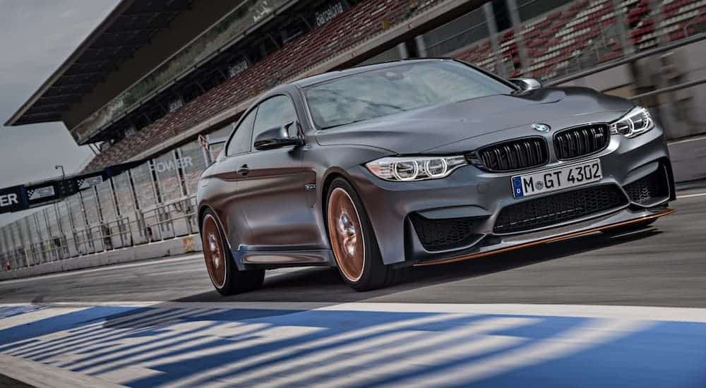 A black 2016 BMW M4 GTS is speeding down the lane at a race track.