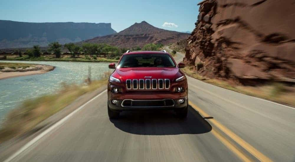 A red 2017 Jeep Cherokee is shown from the front driving on a highway next to a river.