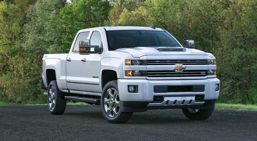 A white 2017 Chevy Silverado 2500HD from a used truck dealer is parked in front of trees.