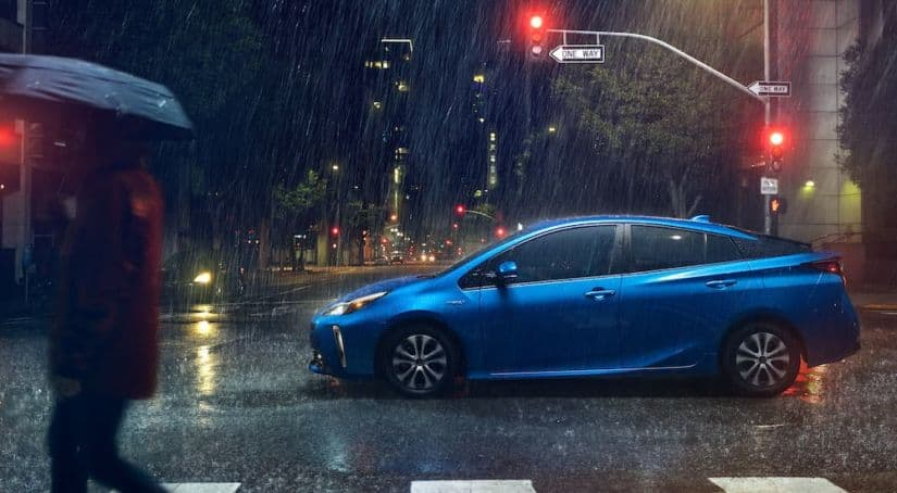 A blue 2021 Toyota Prius is shown from the side driving in a city in the rain at night.