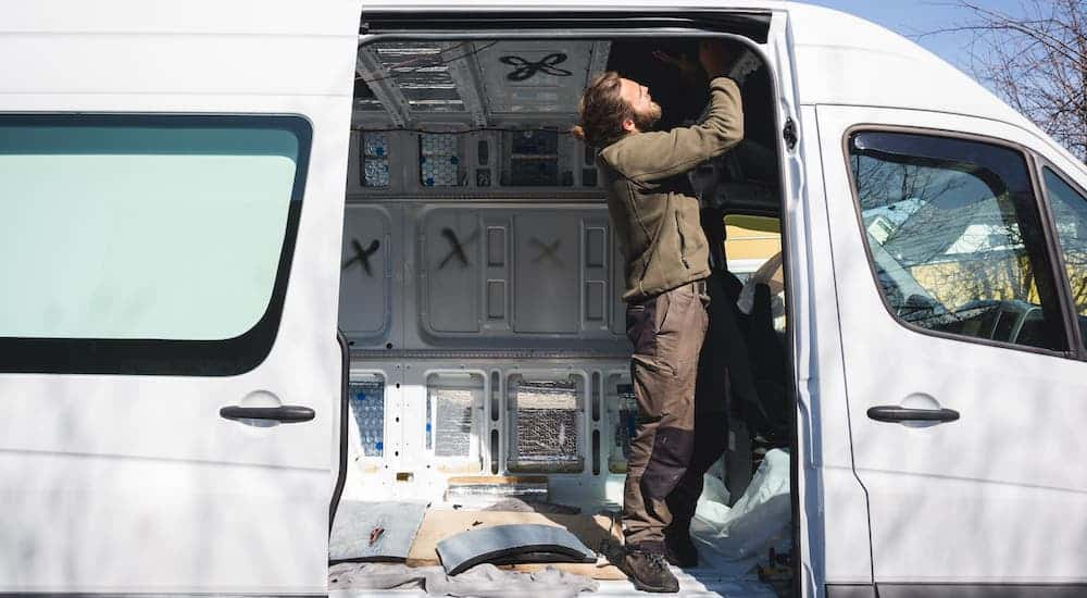 A man is shown inside the open door of a white commercial van that is being converted into a camper.