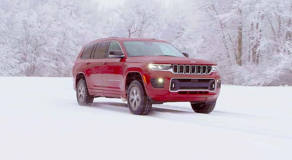 A red 2021 Jeep Grand Cherokee L is shown from the side while parked in the snow.