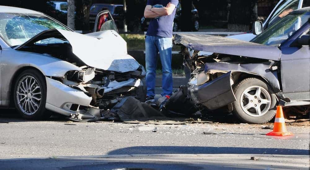 A man is shown standing between two cars after a collision.